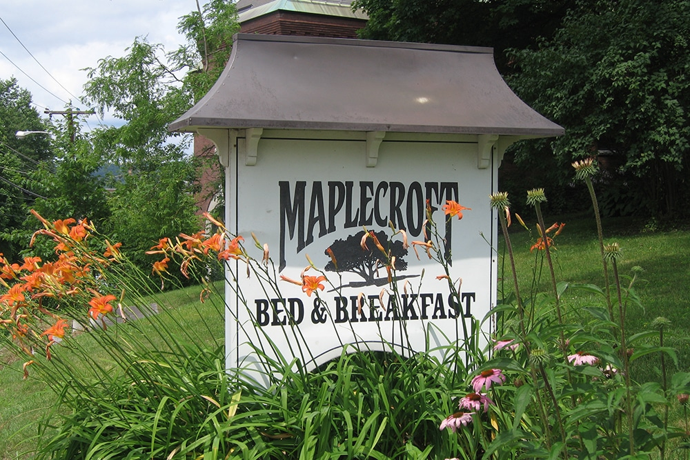 Maplecroft sign in spring, tiger lilies and daisies around the bottom of the sign