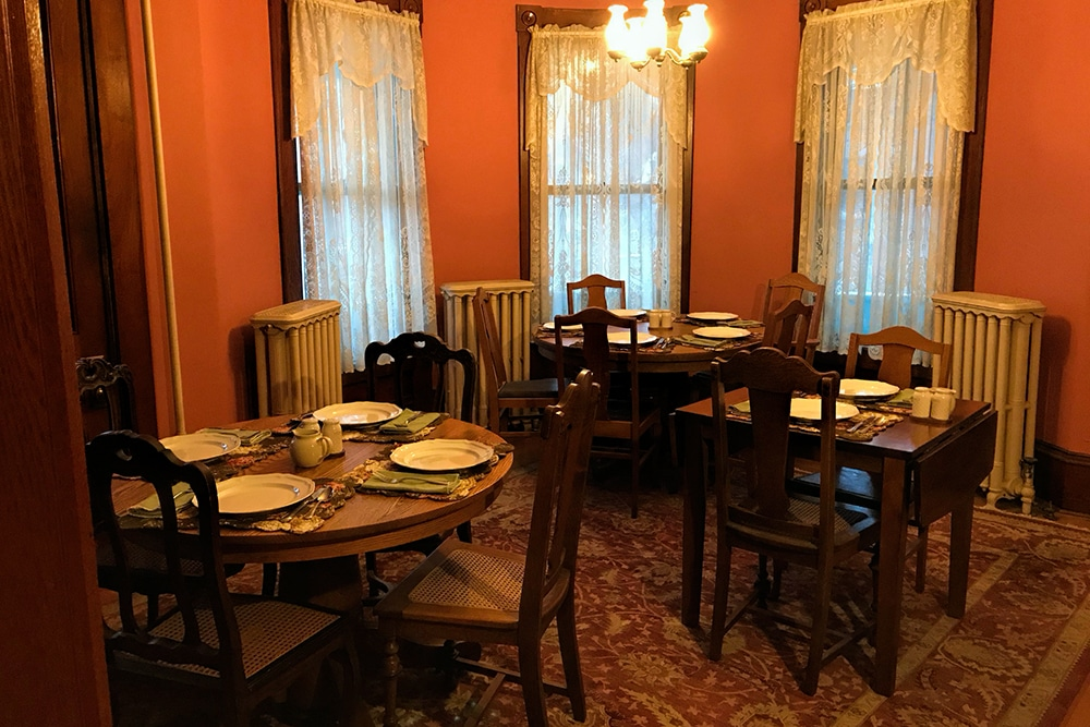 3 tables with chairs set for breakfast in the dining room 3 tall windows rose colored walls and 3 ornate radiators and oriental ru