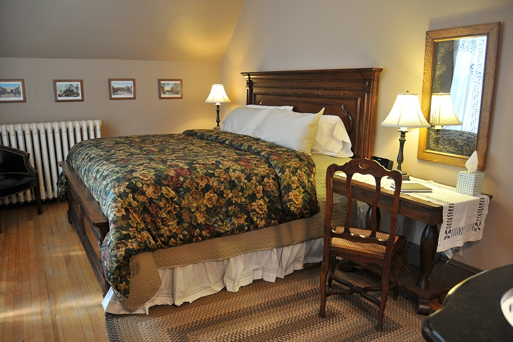 Large wooden headboard and footboard on generous king bed with floral patterned comforter. Wooden end table with lamp. Wood desk and chair with lamp. Beige walls with white radiator