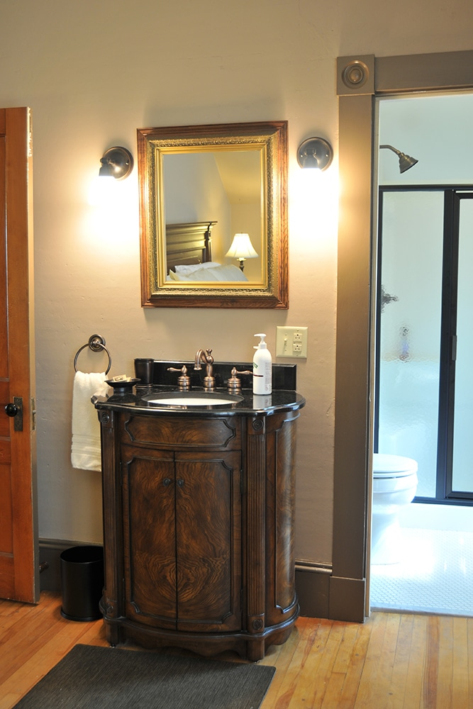 Carved wood and black marble vanity with brushed Nichol fixtures, white hand towel and whit hand soap. Gold framed mirror above. Glimpse of newly renovated bathroom in the background. White tile and white commode
