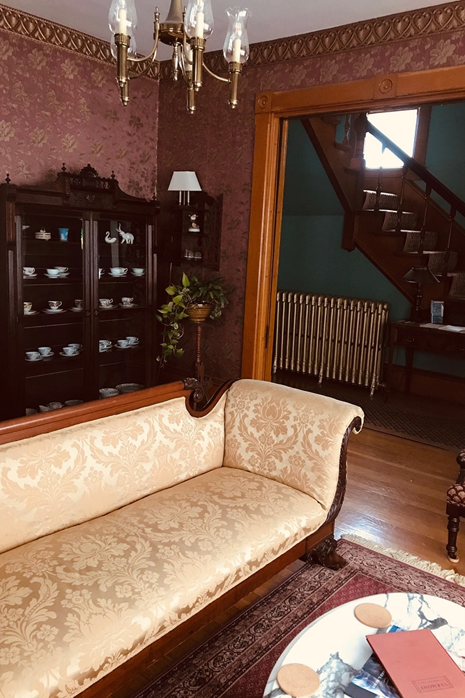 Front entry way with red wallpaper, oak carved doorway, victorian brocade sofa, and fine mahogany china cabinet with tea cups