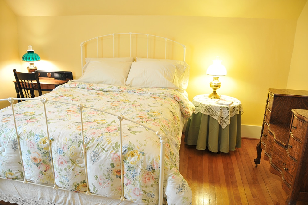 Yellow walls with queen bed. White metal head and foot boards with floral comforter. hard wood floor, antique writing desk and chair with antique lamp and round end table with antique lamp, ornate wood dresser.