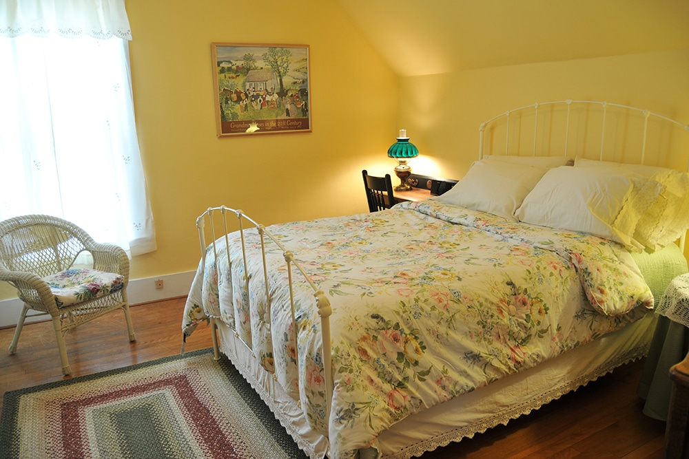 Yellow walls with queen bed. White metal head and foot boards with floral comforter. Braided rug, antique writing desk and chair with antique lamp and Vermont framed poster on the wall.