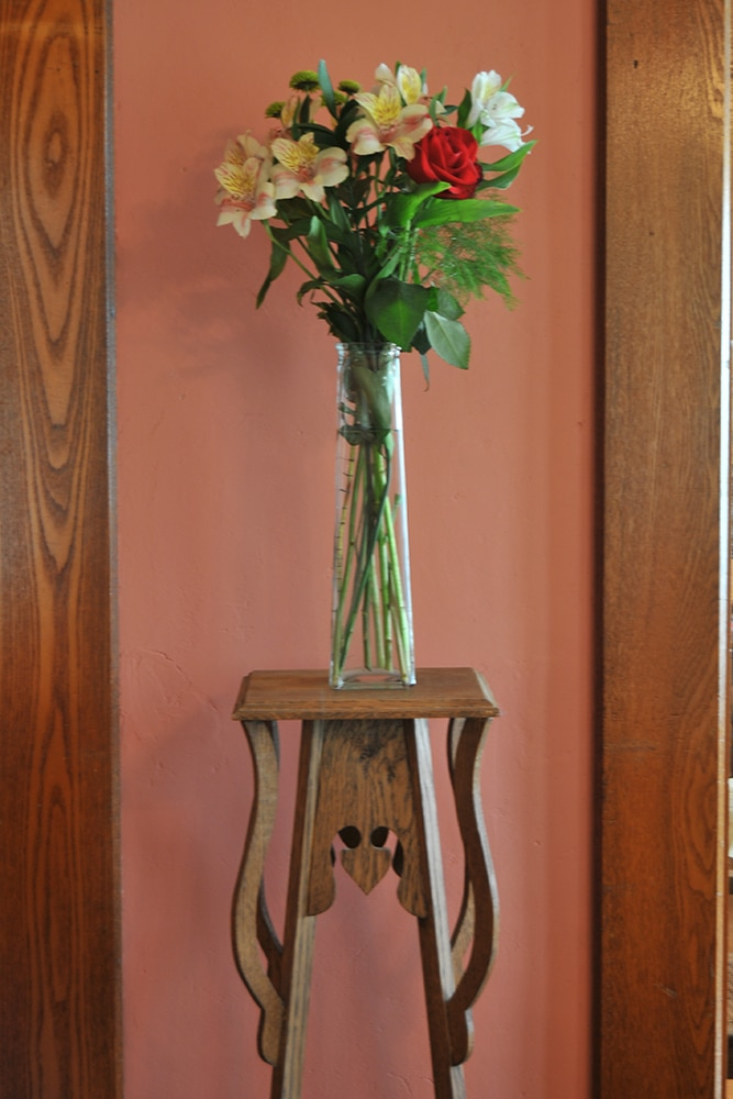 Rose and Lillies in glass vase on wooden plant stand against rose colored wall