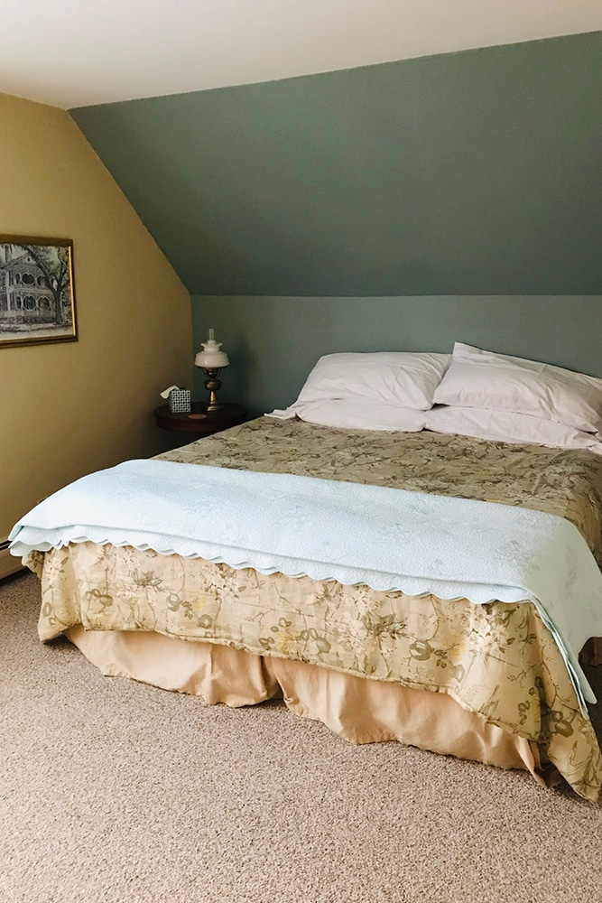 King bed in yellow and green themed room with a brocade conforter