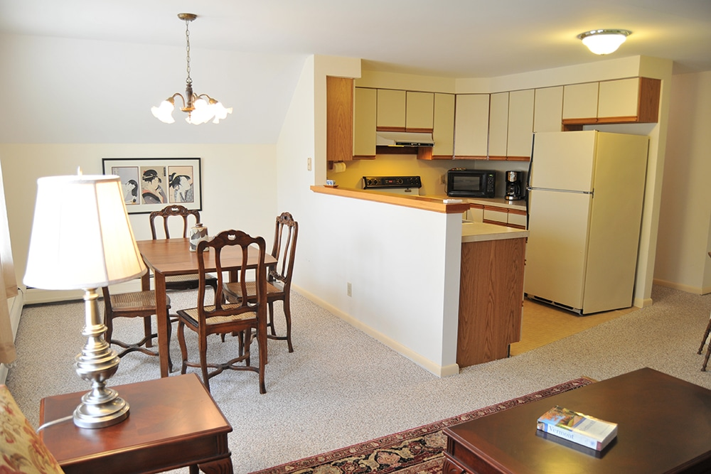 Dining area with wood tables and 4 matching chairs, carpeted floor with wood end table, lamp and area rug in the foreground. Kitchen with full size refrigerator, full size stove, microwave, coffee maker and white cabinets
