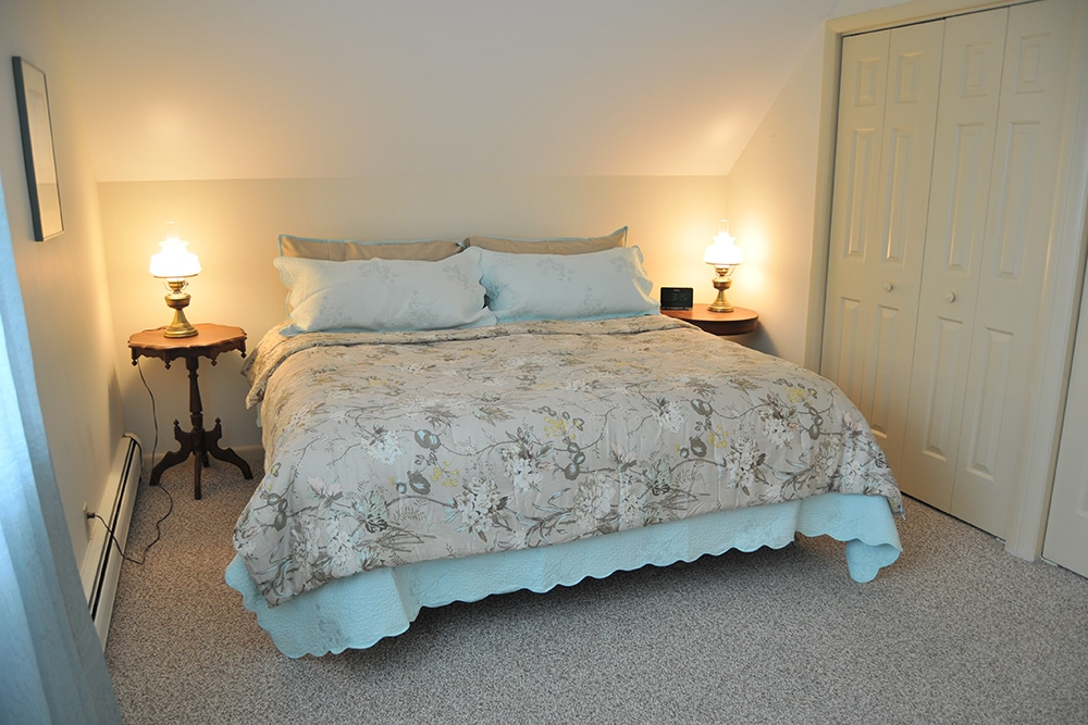 King bed with beige comforter and blue linens, wooden night stands with antique lamps on either side accordion closet doors and tan carpeting