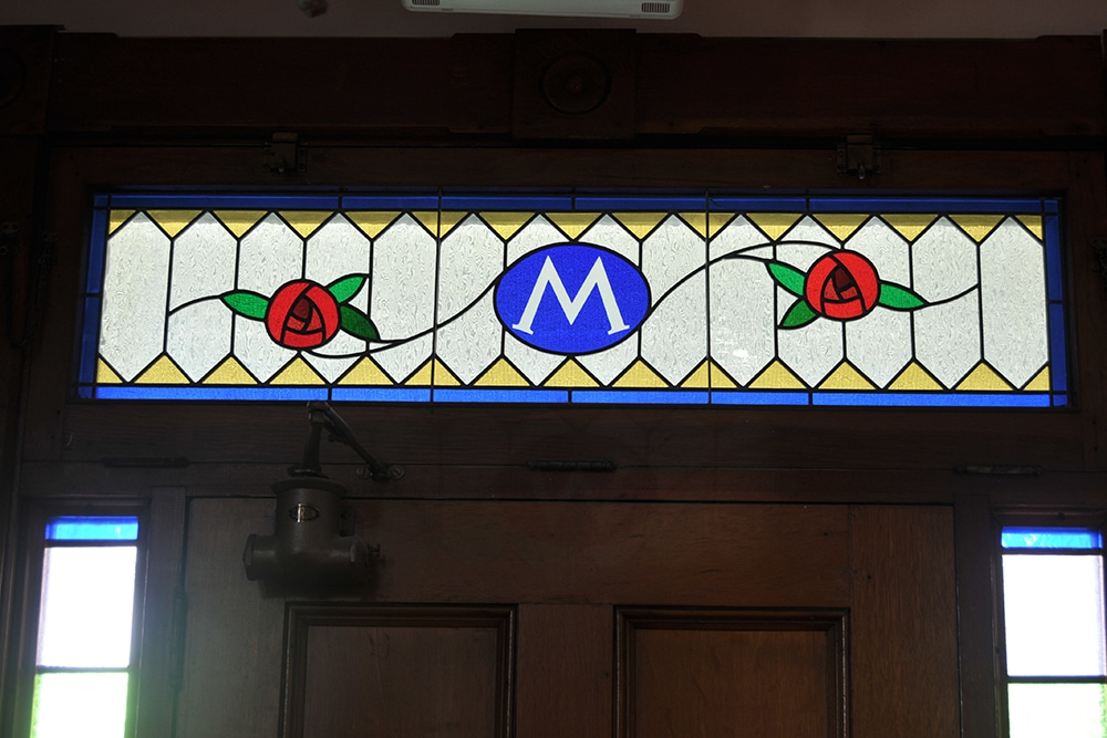 Stained glass transom over front door, M and a rose on each side