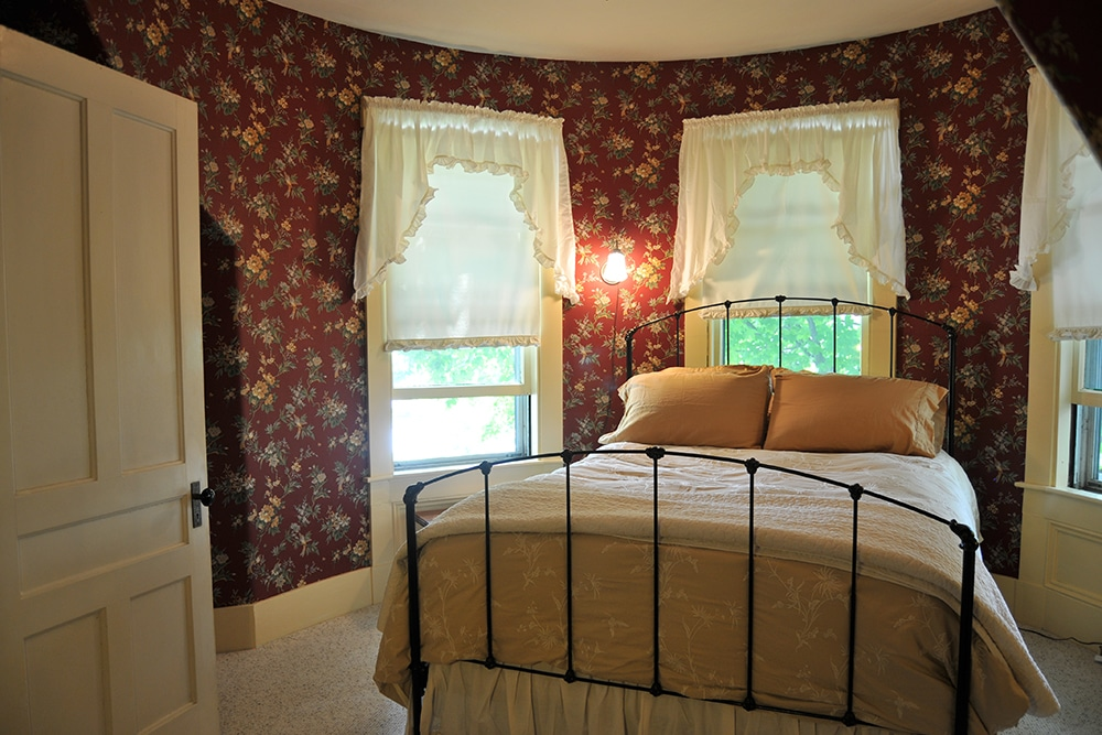 Round room with wallpaper red background with cream and green flowers beige, carpet. Queen bed with metal head and foot board. cream and white comforter with white throw blanket and bed skirt. 3 large windows with white window treatments