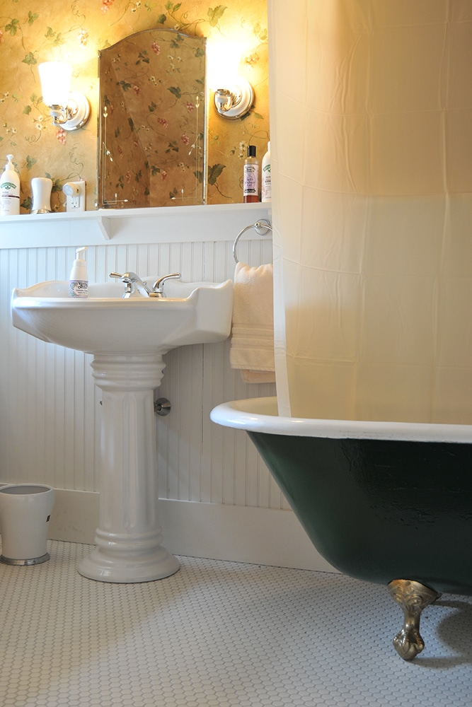 White penny tile floor with white wainscoting , White pedestal sink with silver fixtures and assorted hand soaps and lotions. White ceramic trash bin. Yellow, green and white flowered wall paper, large clawfoot tub