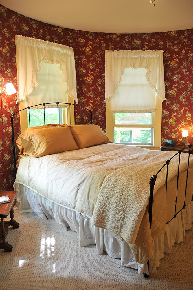 Round room with wallpaper red background with cream and green flowers beige, carpet. Queen bed with metal head and foot board. cream and white comforter with white throw blanket and bed skirt. Wood end tables with antique lamp. 2 Widows with white window treatments